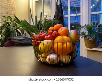 Basket with health, fresh fruit and vegetables in bright colours at a kitchen. Lemon, pepper, mandarin, garlic, apple, tomato, ginger