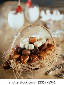 Basket with heart-shaped chocolates with two glasses of coktail still life composition