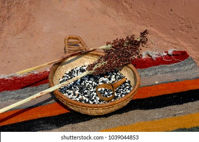 Basket holds dried beans and gourd dipper.  It sits on a colorful Mexican rug on an adobe hearth.