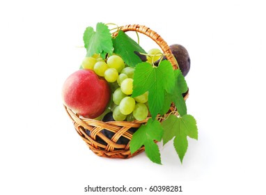 Basket with juicy grapes, apples, plums and figs isolated on white