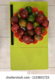 a basket of kiwi fruit, guava, green oranges on green table