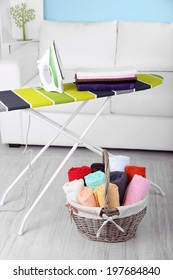 Basket with laundry and ironing board on home interior background