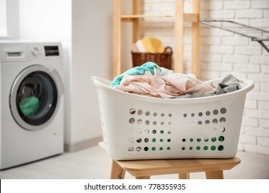 Basket with laundry on stool and washing machine in bathroom