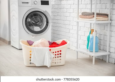 Basket with laundry and washing machine in bathroom