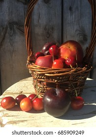 Basket of mixed fruit on an old white stool with a rustic wood background