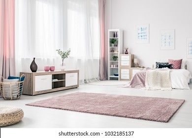 Basket next to a wooden cupboard in spacious bedroom interior with pink drapes and carpet