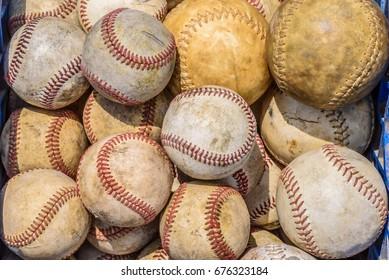 Basket of old baseballs and softballs in daylight