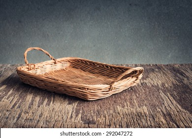Basket on wooden table over grunge background, rustic style