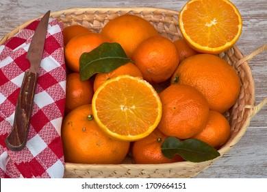 Basket with oranges, mandarins and knife on a napkin