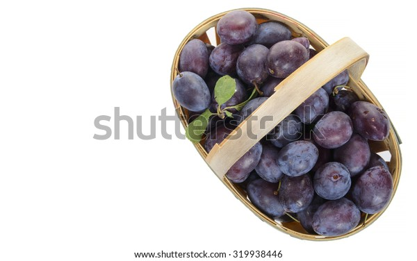 basket of plums on a white background
