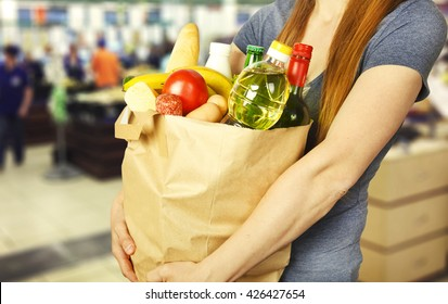 Basket with produce in woman hand on background from supermarket