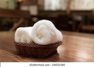 Basket of pure white towels on wooden table in japanese restaurant