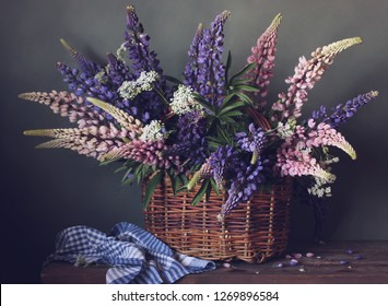basket of purple and pink lupines on the table. garden flowers.