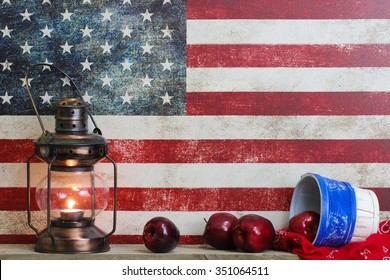 Basket of red apples, bandanna, and antique lantern by vintage American canvas flag  background