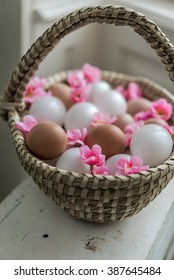 Basket with red easter eggs on rustic white wooden table