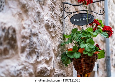 Basket with red flowers and plaque with words Feel a t Home hanging from the house wall next to the front doors