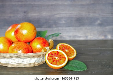 basket with ripe oranges and orange halves on a wooden table. oranges and green leaves close-up. background with oranges and half oranges.
