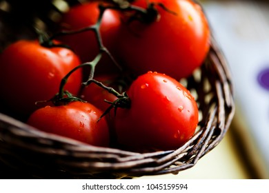 A basket of ripe tomatoes on kitchen table