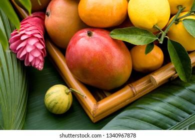 Basket of ripe tropical fruits: lemons, mangoes and tangerines