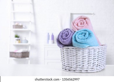 Basket with rolled fresh towels on table in bathroom. Space for text