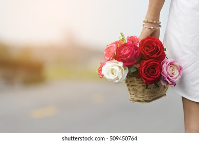 Basket of rose flowers in Valentine's Day,Beautiful woman wearing a white dress shirt standing and holding flower to surprise boyfriend .Valentine Day concept
