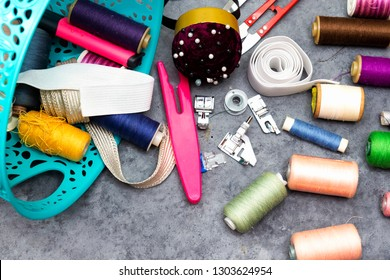 basket of sewing tools :  scissors, colorful  bobbins with thread and presser foot on gray  wooden table