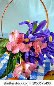 Basket with spring iris flowers and Peruvian lilies, apples  on the blue-white checked tablecloth,  vertical view, spring background, 8 March postcard