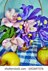Basket with spring iris flowers and Peruvian lilies, apples  on the blue-white checked tablecloth,  vertical view, spring background, postacrd for 8 March, Happy Birthday