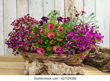 A basket with springtime flowers decorated with wood.