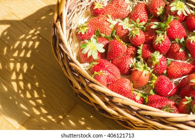 Basket with strawberry on table, sunny shadow