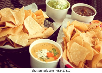 Basket of tortilla chips, queso, guacamole and salsa, vintage toned