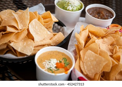 Basket of tortilla chips, queso, guacamole and salsa