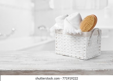 Basket, towels and bath brush on wood over blurred bathroom