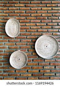 Basket and tray made from dried bamboo decorate on brick wall. Handmade product from Thailand. To decorate house or restuarant. Concept of handmade and nutural conservation