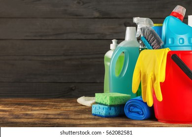 Basket with variety cleaning product on wooden table with copy space