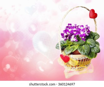 Basket with violets, decorated with hearts and ribbon with a background of soap bubbles in the shape of a heart, with space for your text