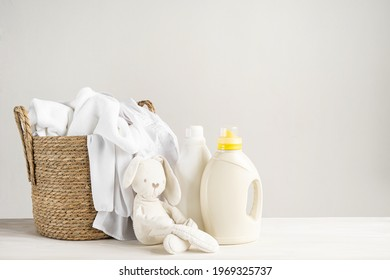A basket of white laundry, a teddy bunny toy, a bottle of liquid detergent, washing gel or fabric softener. Mockup for washing baby clothes with copy space.