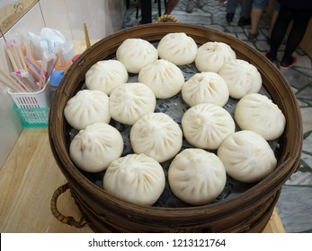 Basket of xiaolongbao (steamed meat bun), famous asian food. Chinese dumplings on bamboo steamer sold at eatery.