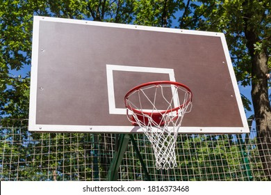 Basketball backboard with basket installed on the outdoor sports field, view on background of the trees branches in park