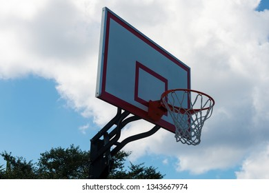 Basketball backboard and hoop against a cloudy sky