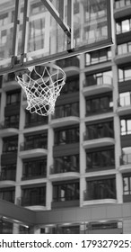 Basketball backboard and hoop on the background of buildings