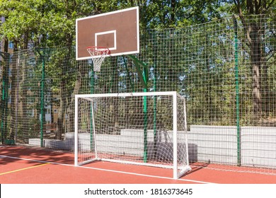 Basketball backboard and mini football goal on the universal outdoor sports field in park against the trees