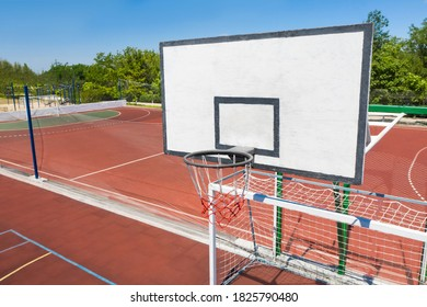 Basketball backboard over football gat at outdoor sports complex on sunny day