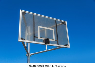 Basketball backboard without a hoop or net. Hoop-less backboard under a blue sky