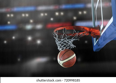 Basketball ball,  board and net in front of big modern basketball arena with flares and lights