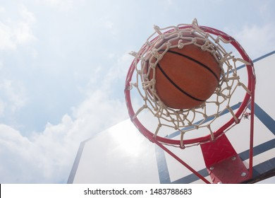 Basketball ball entering the rim and falling through the net, against the blue sky, copy space