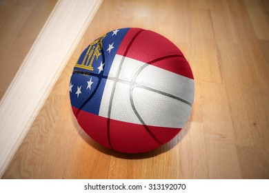 basketball ball with the flag of georgia state lying on the floor near the white line