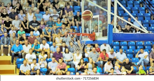 A basketball ball flies into the ring. In the background in the stands are fans