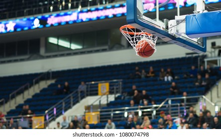 The basketball ball flies through the basket. In the background, a small group of fans sitting in the stands