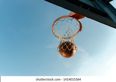 Basketball ball going through a hoop, beautiful natural lighting at sunset